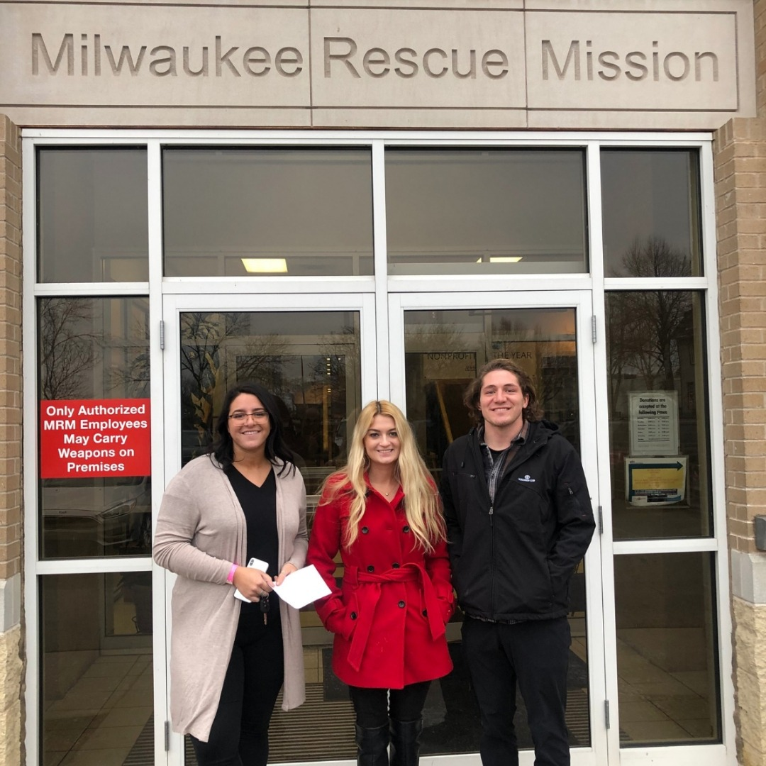 Devon, Alec, and Carly standing in front of the Milwaukee Rescue Mission building